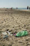 Plast- avskräde som lämnas på en sandig strand Royaltyfri Bild
