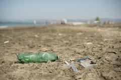 Plast- avskräde som lämnas på en sandig strand Royaltyfri Fotografi