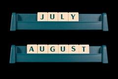 Plast- bokstavstegelplattor Ord inkluderar Juli och Augusti Royaltyfri Foto