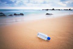Plast- buteljera på stranden fotografering för bildbyråer