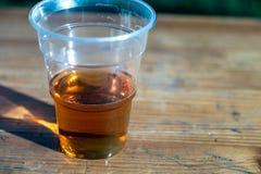 Plast- exponeringsglas med öl på en trätabell arkivbild