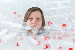 Plast- f?roreningproblem och milj?skydd Svag tr?tt kvinna i en h?g av plast- flaskor R?ddningjordbegrepp arkivfoto