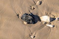 Plast- fackpåsar som tvättas upp på sandstranden i Agadir, Marocko, Afrika arkivbild