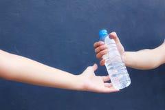 Plast- flaska för manhandrengöring mycket av nytt dricksvatten till kvinnan på bakgrund fotografering för bildbyråer