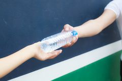 Plast- flaska för manhandrengöring mycket av nytt dricksvatten till kvinnan på isolerad bakgrund royaltyfria foton