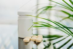 Plast- flaska med spridda ljusa piller på exponeringsglaset arkivbilder