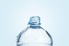 Plast- flaska mycket med vatten på blå bakgrund royaltyfria foton