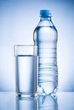 Plast- flaska och exponeringsglas av dricksvatten på blått tillbaka Fotografering för Bildbyråer