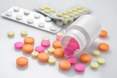 Plast- flaska och hög av piller arkivfoto