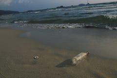 Plast- flaskavskräde på stranden på Trad, Thailand arkivbild
