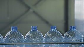 Plast- flaskor fortskrider transportbandet i seminarium av företaget inomhus lager videofilmer