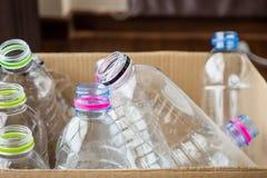 Plast- flaskor, i återanvändning av den pappers- asken, återanvänder begrepp royaltyfria foton