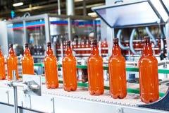 Plast-flaskor med öl eller den kolsyrade drycken som är rörande på transportör royaltyfri fotografi