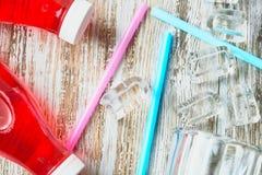 Plast- flaskor med bär, förnyande drink spridda iskuber och dricka sugrör på bakgrunden av ett sjaskigt trä arkivfoton