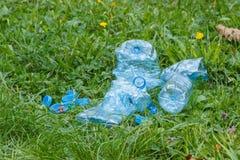 Plast-flaskor och kapsyler på gräs parkerar in, att skräpa ner av miljön Royaltyfri Foto