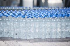 Plast-flaskor på transportbandet Arkivbild