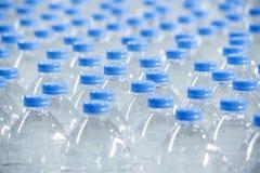 Plast-flaskor på transportbandet Royaltyfri Bild
