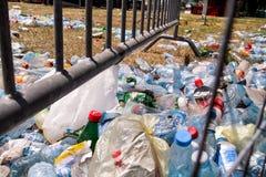 Plast- flaskor som kastas av metallstaketet Använda tomma husdjurflaskor som bort kastas och lämnas på gräs efter ett parti för ö Arkivbild