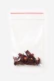 Plast- genomskinlig blixtlåspåse med lite carcadete som isoleras på vit, vakuumpackemodell med det röda gemet Begrepp Arkivbilder