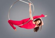 Plast- härlig flickagymnast på den akrobatiska cirkuscirkeln i kött-färgad dräkt Fotografering för Bildbyråer