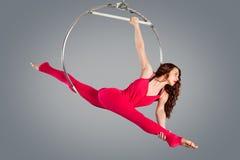 Plast- härlig flickagymnast på den akrobatiska cirkuscirkeln i kött-färgad dräkt arkivbild