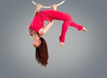 Plast- härlig flickagymnast på den akrobatiska cirkuscirkeln i kött-färgad dräkt arkivfoton