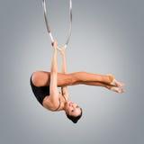 Plast- härlig flickagymnast på den akrobatiska cirkuscirkeln i kött-färgad dräkt royaltyfri foto