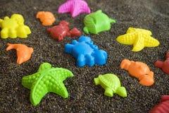 Plast- havsdjur på man gjord sand Leksaksamling som isoleras på vit bakgrund Royaltyfria Foton