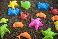 Plast- havsdjur på man gjord sand Leksaksamling som isoleras på vit bakgrund Royaltyfri Foto