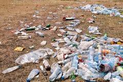 Plast-husdjurflaskor som lämnas på gräs efter ett parti, händelse Använda tomglas som bort kastas på jordningen efter ett parti f Royaltyfri Bild