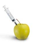 Plast- injektionsspruta i grönt äpple Arkivbilder