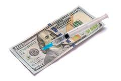 Plast- injektionsspruta med injektionlösningen på 100 dollarräkningar Läkarundersökning och affärsidé bakgrund isolerad white arkivfoto