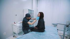 Plast- kirurg som kontrollerar den mitt åldrades kvinnaframsidan för kosmetisk kirurgi lager videofilmer