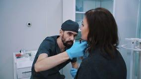 Plast- kirurg som kontrollerar den mitt åldrades kvinnaframsidan för kosmetisk kirurgi arkivfilmer