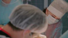 Plast- kirurger som avslutar operationen med att sy ihop användande steriliserad utrustning arkivfilmer
