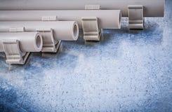 Plast- klämmor för vattenrörrör på metallisk bakgrundstankeskapelse Royaltyfri Fotografi