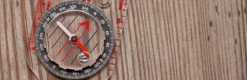 Plast- kompass över en träbakgrund Arkivbilder