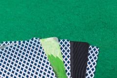 Plast- kontokort ligger med kort för att spela poker på torkduken för den gröna tabellen royaltyfria bilder