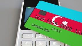 Plast- kontokort som presenterar flaggan av Azerbajdzjan och pos.-betalningterminalen Azerbajdzjansk banksystem eller återförsälj stock video