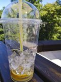 Plast- kopp med lemonadkvarlevor på tabellen utomhus royaltyfri bild