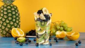 Plast- kopp med skivad fruktsallad på gul bakgrund arkivfilmer