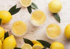 Plast- koppar med den kräm- och ljusbruna efterrätten för citron Arkivfoto