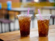 Plast- koppexponeringsglas av colacola eller cola på den wood tabellen på vilar Arkivfoto