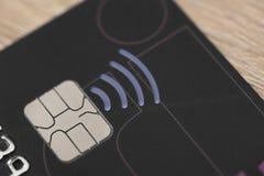 Plast- kreditkort med chipen och pengar för contactless symbol den elektroniska Arkivfoto
