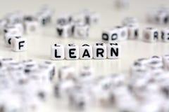 Plast- kuber märker att bilda ordet för att lära på vit bakgrund arkivbild