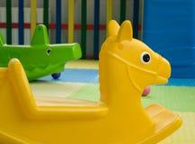 Plast- leksakhäst-stolar och krokodil royaltyfri foto