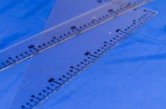 Plast- linjaler med blå bakgrund, med mätningar i cm och meter Arkivbilder