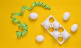 Plast- magasin med vita ägg och en linjal på en gul pastellfärgad bakgrund, minimalismtrend, bästa sikt arkivfoto