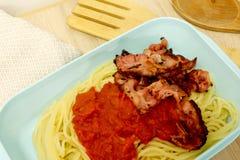 Plast- matbehållare som fylls med bacon, tomatsås och spagetti arkivfoton