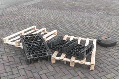 Plast- och träpaletter på gatan royaltyfri foto